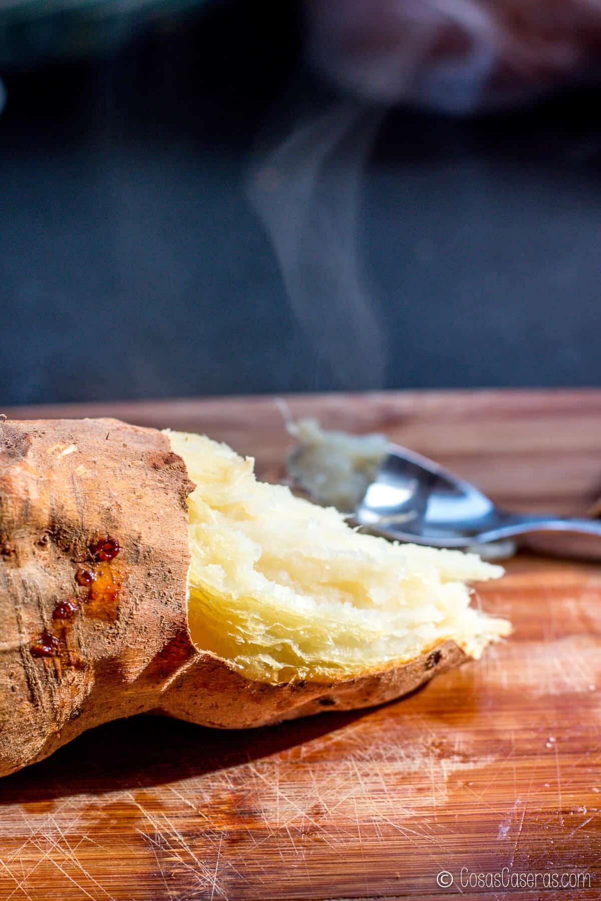 Un boniato horneado que está parcialmente pelado, con vapor saliendo de la parte abierta del boniato.
