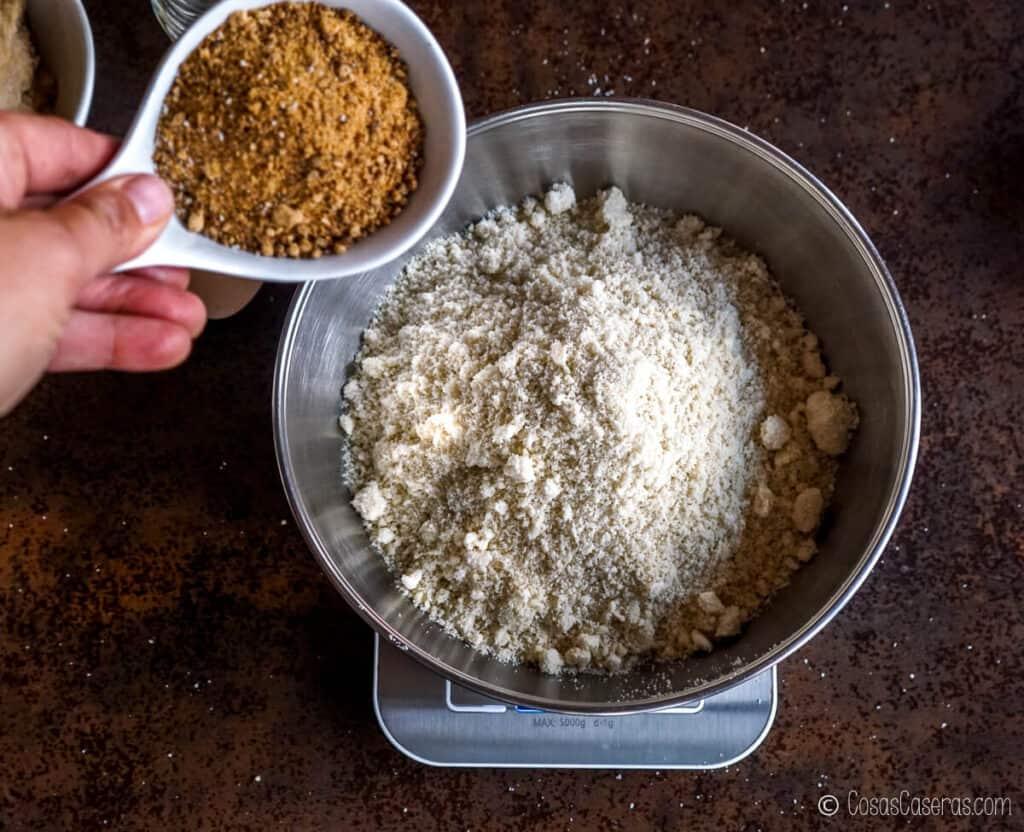 Vertiendo azúcar en un bol con harina de almendras.
