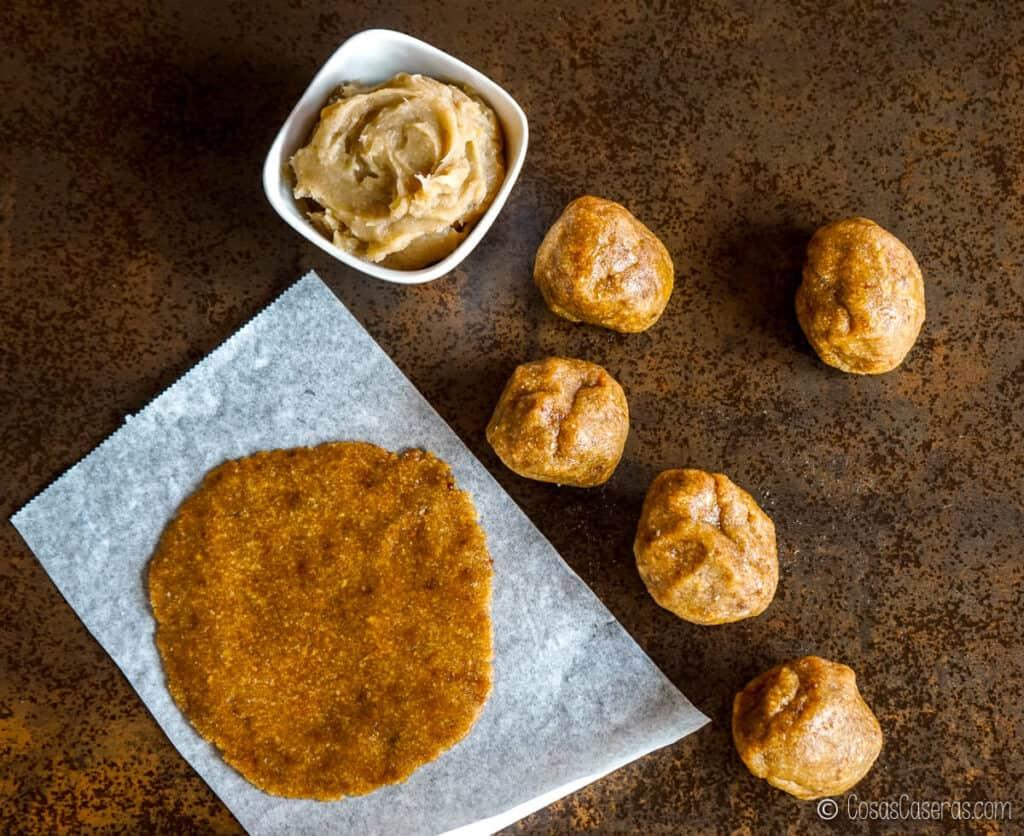 Vista aérea de un círculo de masa para pastissets sobre papel de horno, junto a otras bolas de masa y un cuenco de dulce de boniato