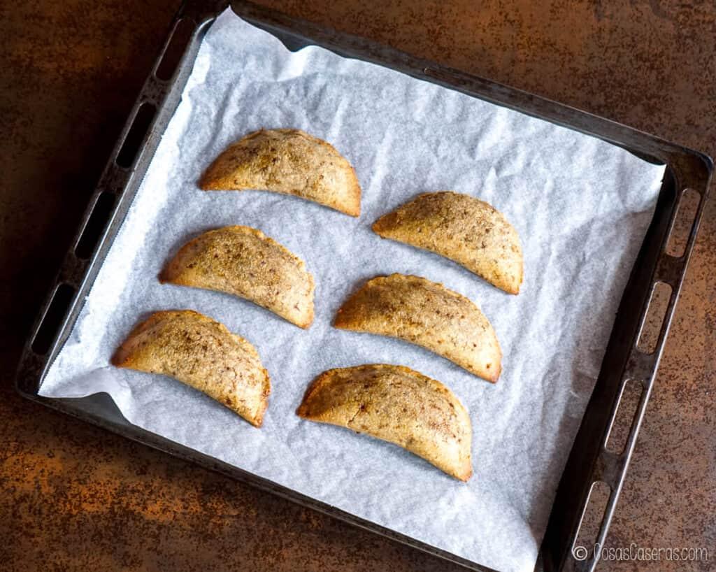 Vista aérea de varios pastissets caseros en una bandeja para hornear.