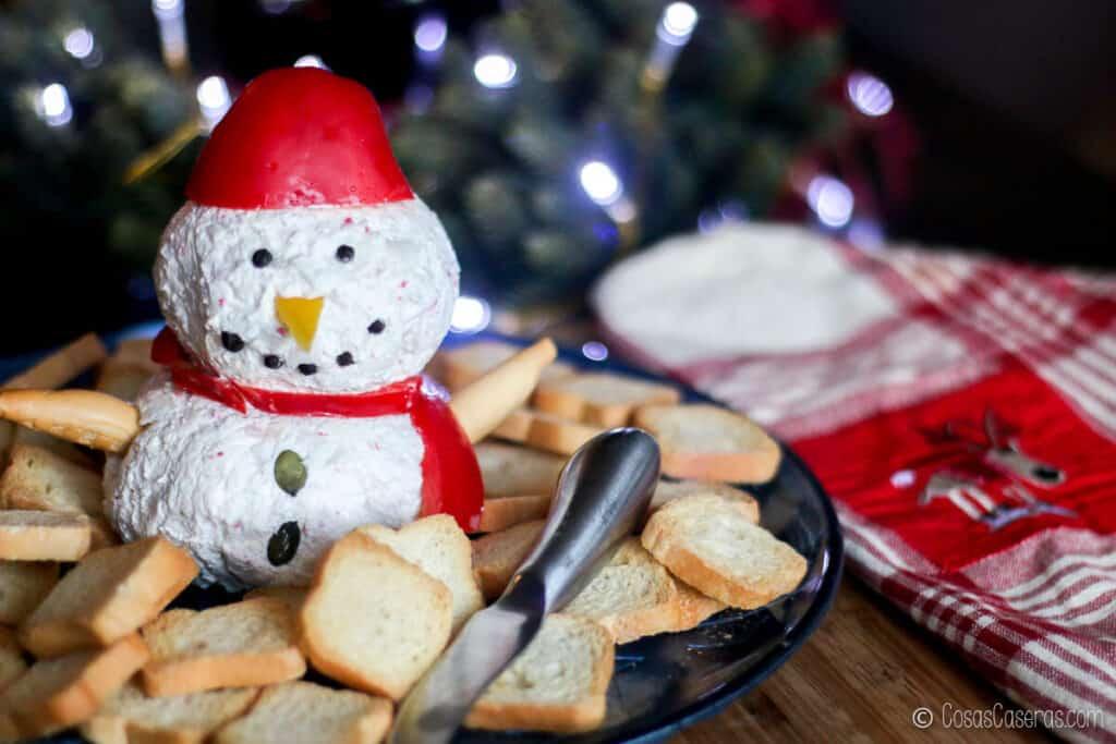 Una bola de queso de muñeco de nieve en una bandeja rodeada de galletas junto a una toalla navideña.