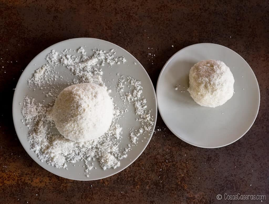Dos bolas de queso recubiertas de galletas trituradas.