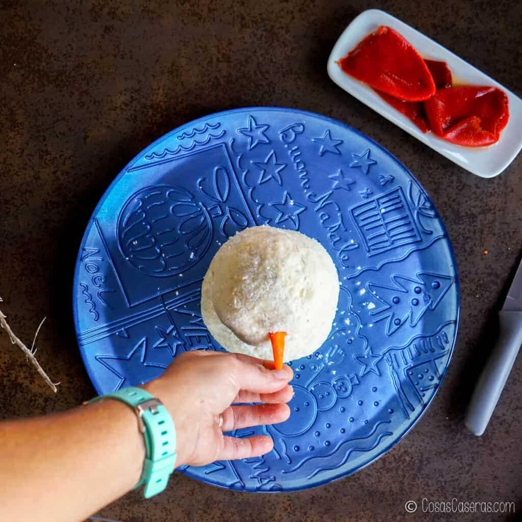 Colocando la punta de la zanahoria en la bola de queso superior