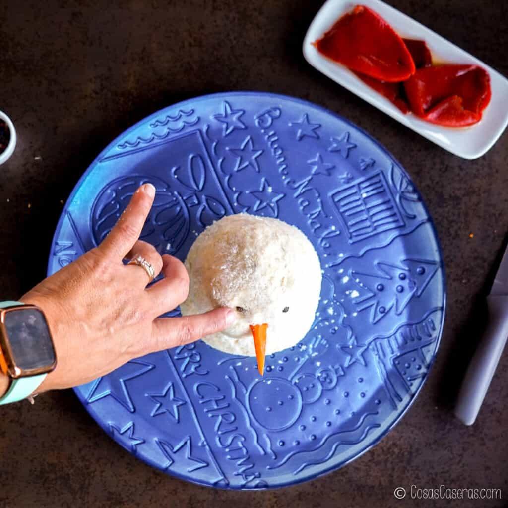 Presionando los granos de pimienta en la bola de queso