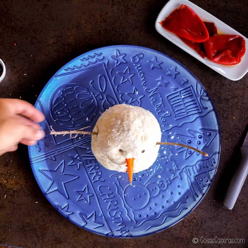 metiendo las ramas de romero en los lados de la bola de queso