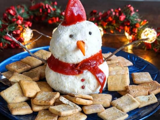 Una bola de queso de muñeco de nieve rodeada de galletas.
