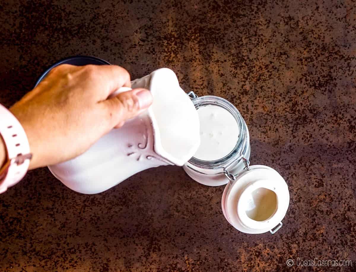Vertiendo la nata en un frasco de vidrio