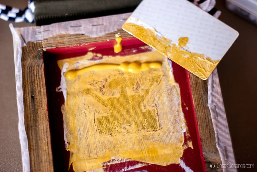 colocando pintura de tela en el marco de serigrafía con una tarjeta