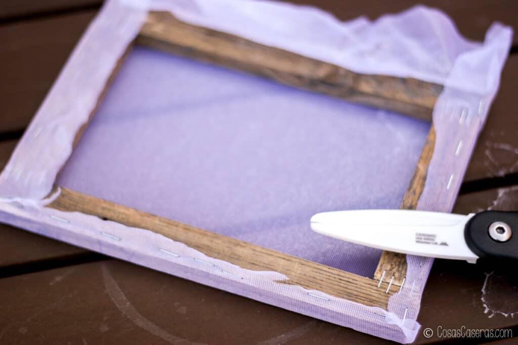 cortando el exceso de tela de un marco con tela