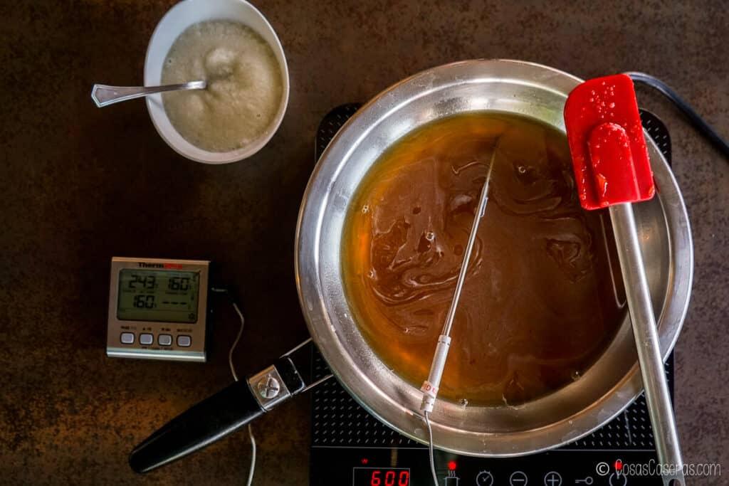 Vista aérea de una mezcla de agua y miel en una sartén con una sonda de termómetro dentro. La gelatina se hidrata en un recipiente blanco al lado.