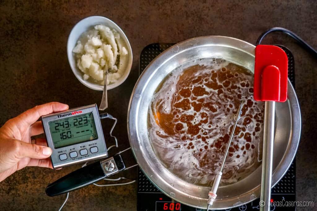 Vista aérea de una mezcla de miel con una lectura de termómetro de 243ºF. Al lado hay un recipiente con gelatina hidratada.