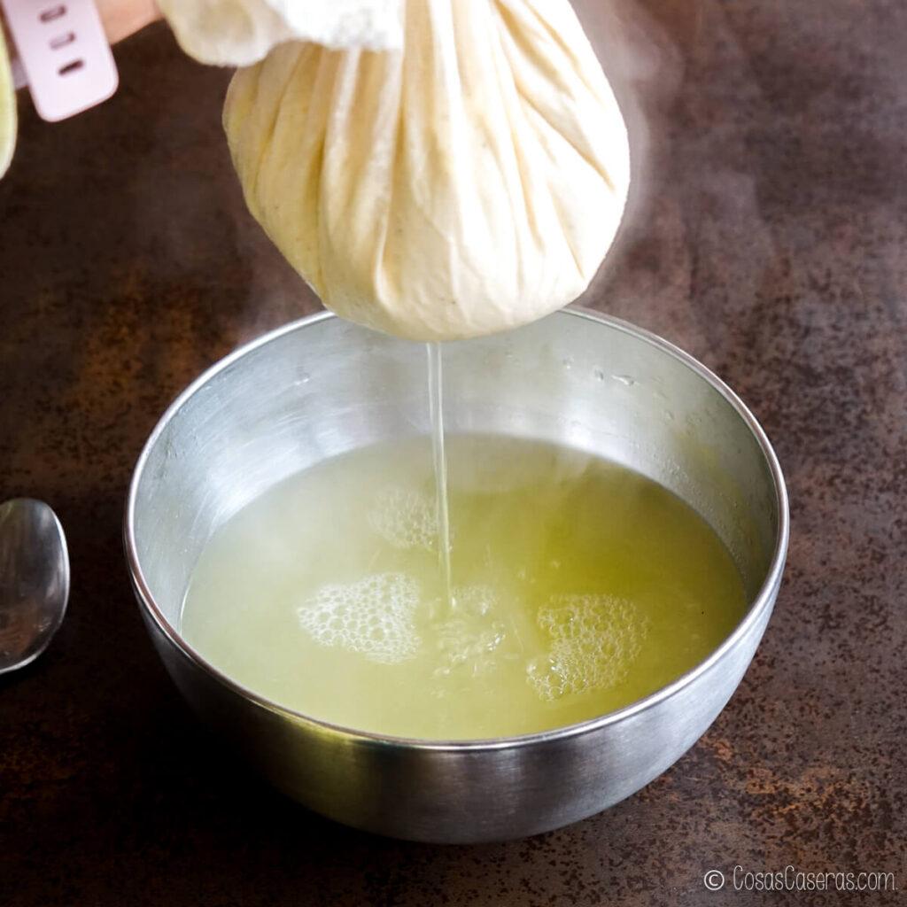 Levantando la gasa llena de la leche cuajada sobre un bol, dejando que se filtra el suero al bol