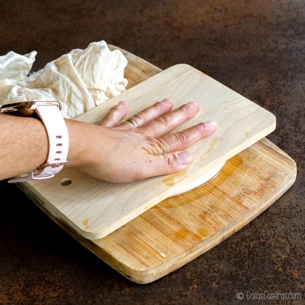 Aplastando el queso con una tabla de cortar