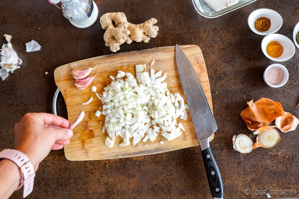 Pelando ajos sobre una tabla de cortar con cebolla picada
