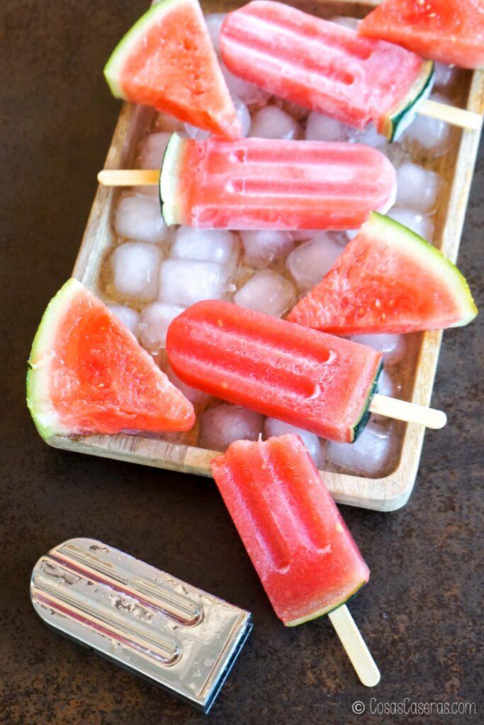 Polos de sandía y gelatina decorados con corteza de sandía en una bandeja con hielo