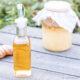 una botella de vinegare de Jengibre delante de un bote con más vinagre fermentando