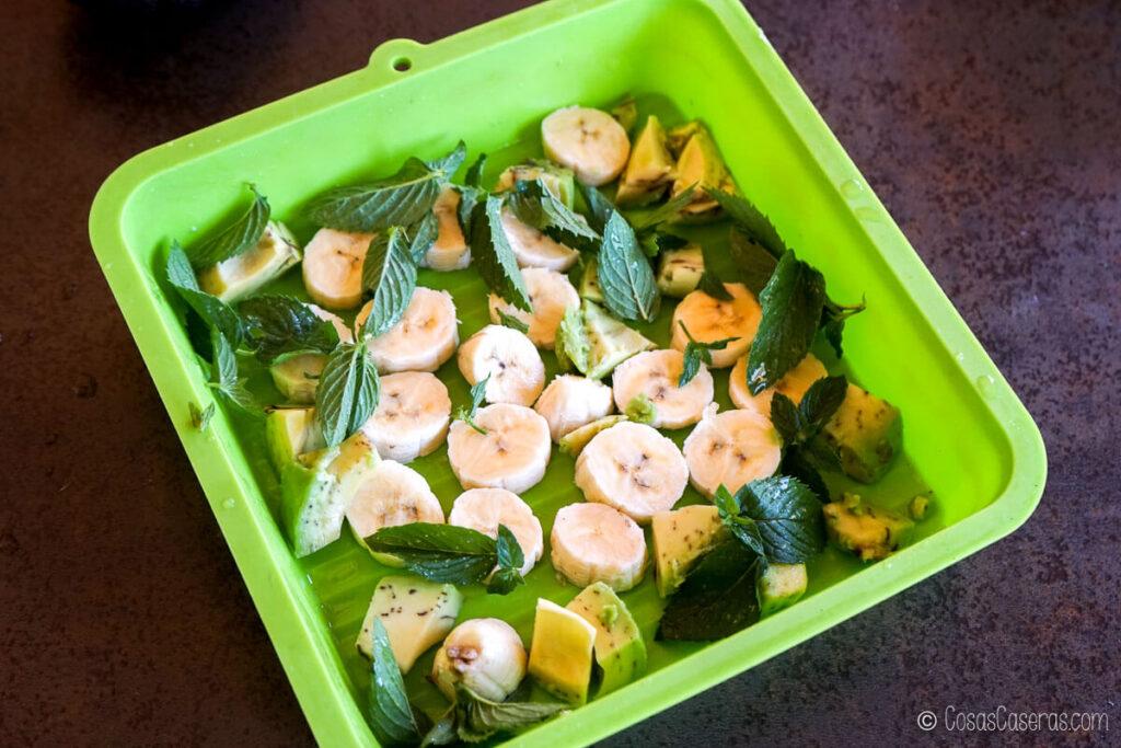 Rodajas de plátano y hojas de menta congelados en un molde de silicona
