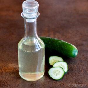 una botella de extracto de pepino al lado de un pepino y unos trocitos de pepino