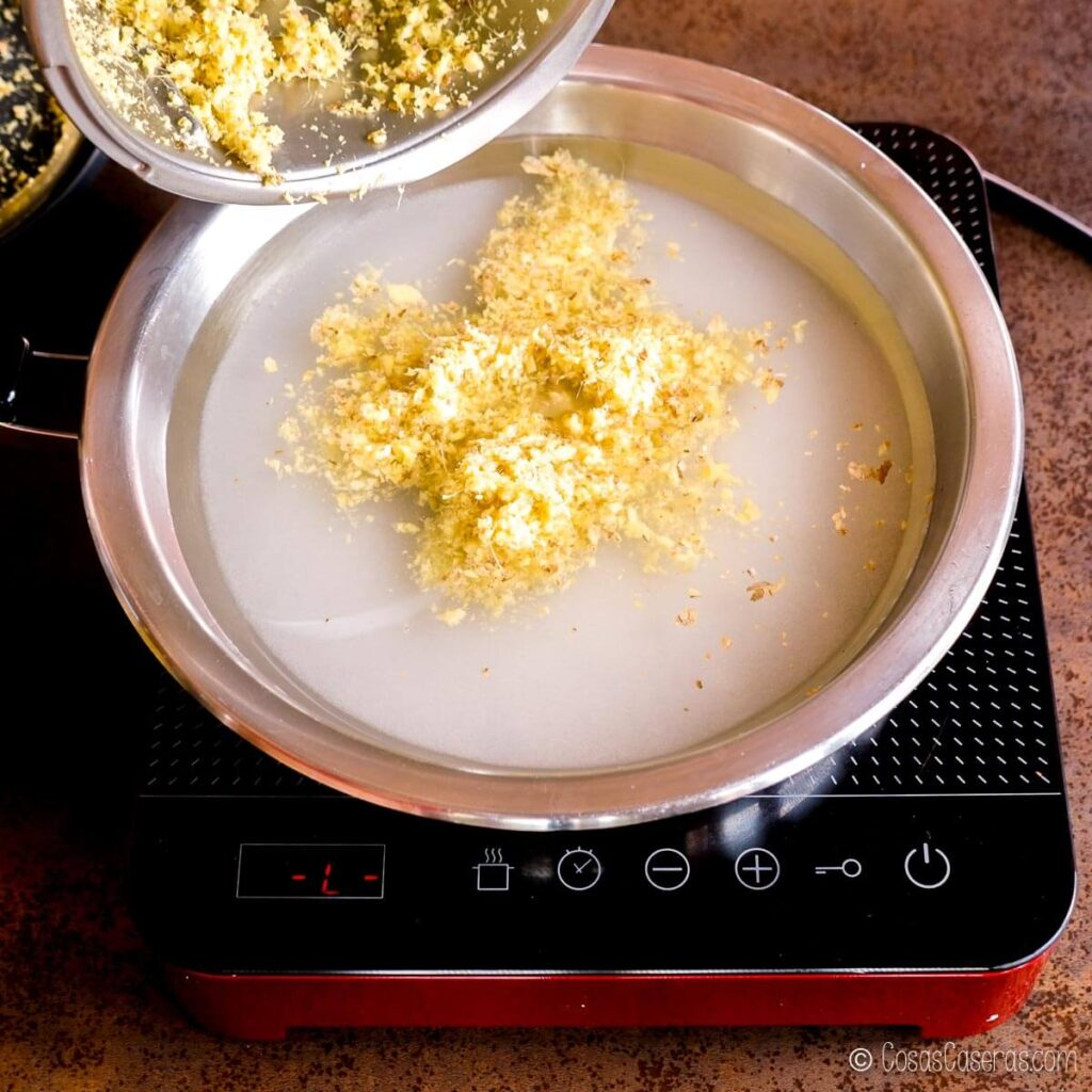 echando jengibre picado a una sartén con agua y azúcar