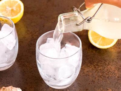 Vertiendo ginger beer casero en un vaso con hielo